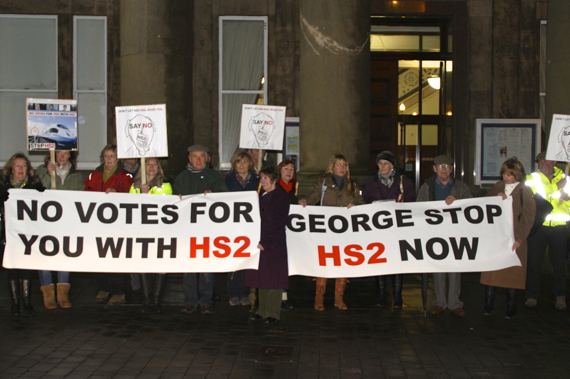 "Protest outside George Osborne's meeting with Parish Councillors: signs read ""no votes for you with HS2"" and ""George Stop HS2 now"""