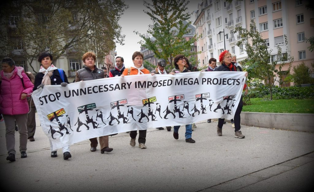 Shows banner against 'unnecessary, imposed mega projects'